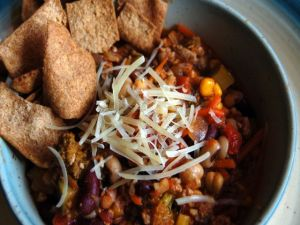 Hearty Three-Bean Soup with pita chips and shredded Parmesan